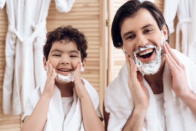Vader en zoon bedekken het hele gezicht met scheerschuim.