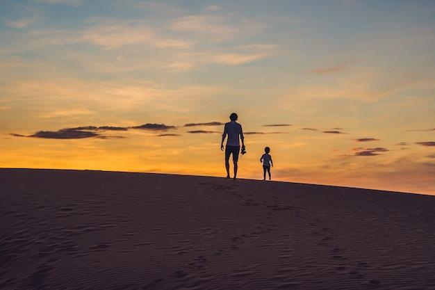 Vader en zoon bij de rode woestijn bij dageraad die met kinderen reizen Premium Foto