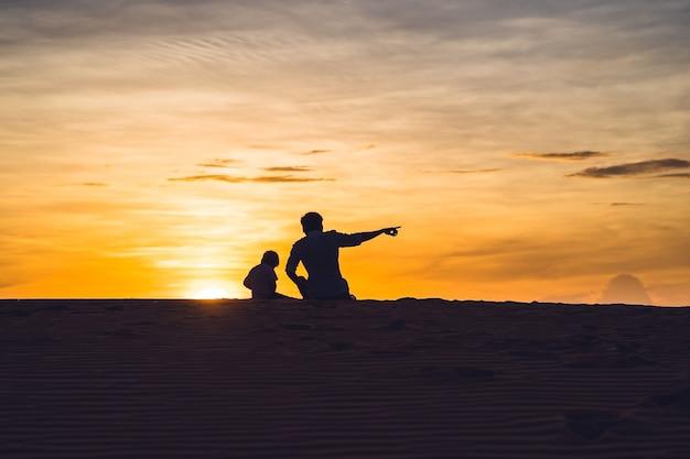 Vader en zoon bij de rode woestijn bij dageraad. reizen met kinderen concept
