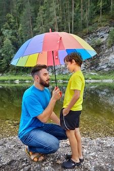 Vader en zoon brengen vaderdag door op het platteland in de buurt van de rivier, vader houdt een paraplu boven zijn kind om hem tegen regen te beschermen.