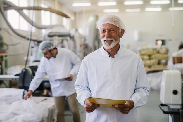 Vader en zoon controleren producten in hun voedselfabriek. volwassen man in steriele kleren staan voor de camera met een glimlach op zijn gezicht. succesvol bedrijfsconcept.
