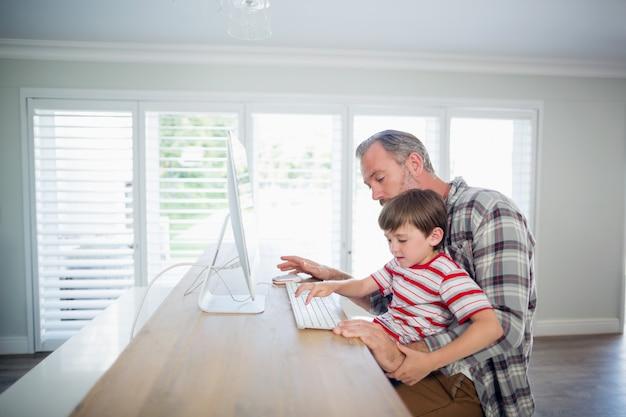 Vader en zoon die aan computer werken