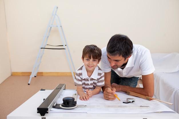 Vader en zoon die architectuur thuis bestuderen