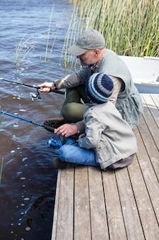 Vader en zoon die bij een meer vissen