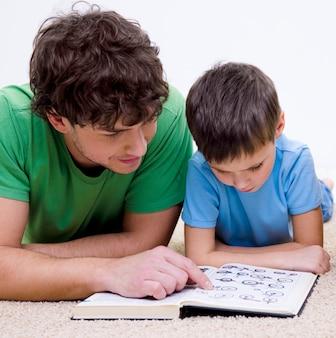 Vader en zoon die binnenshuis boek lezen dat op vloer ligt