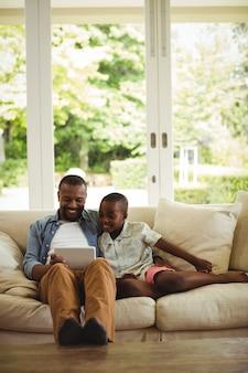 Vader en zoon die digitale tablet in woonkamer gebruiken