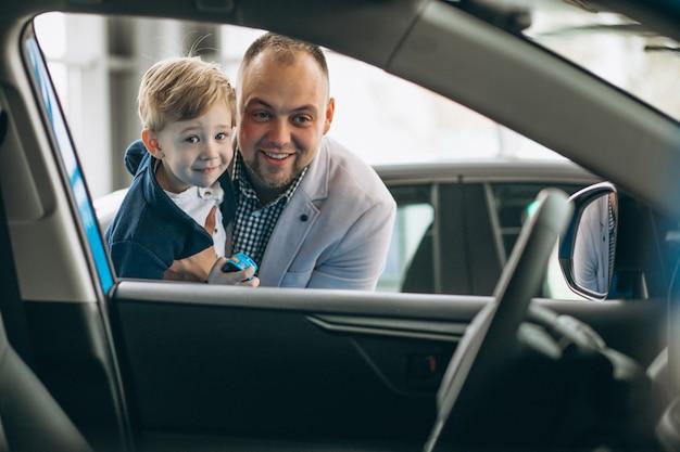 Vader en zoon die een auto in een autotoonzaal bekijken