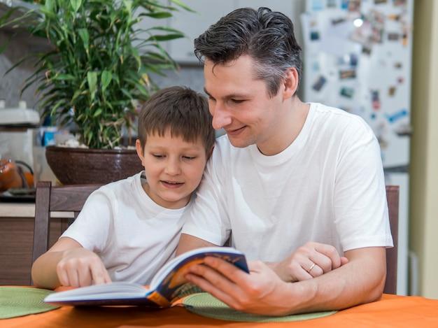 Vader en zoon die een boek middelgroot schot lezen