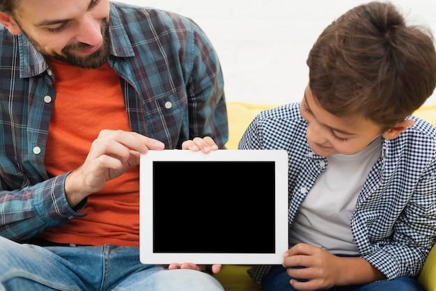 Vader en zoon die een onechte foto tegenhouden