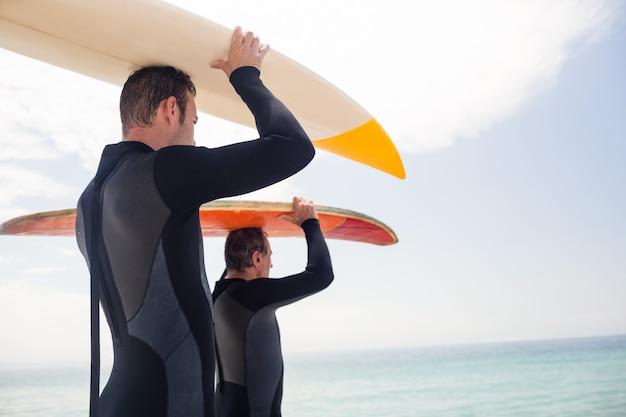 Vader en zoon die een surfplank over hun hoofd dragen