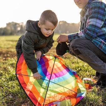 Vader en zoon die een vlieger repareren