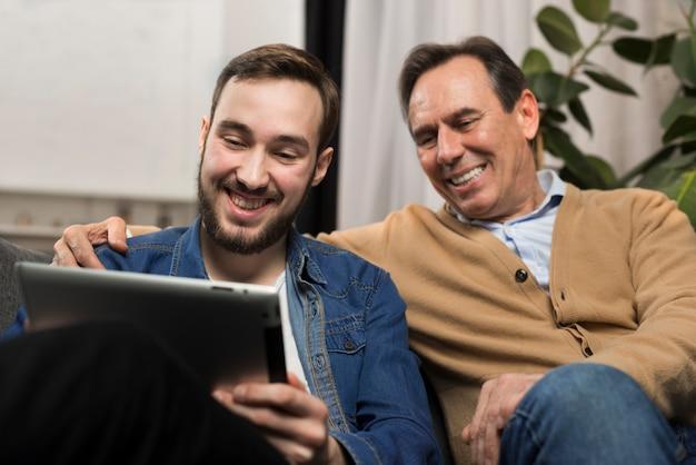 Vader en zoon die en tablet in woonkamer glimlachen bekijken