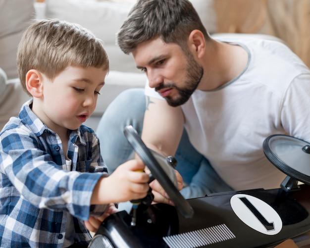 Vader en zoon die het raceauto middelgrote schot bevestigen