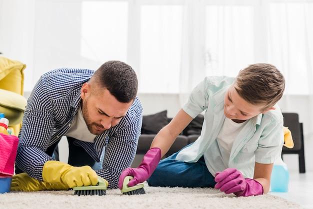 Vader en zoon die het tapijt met borstels schoonmaken