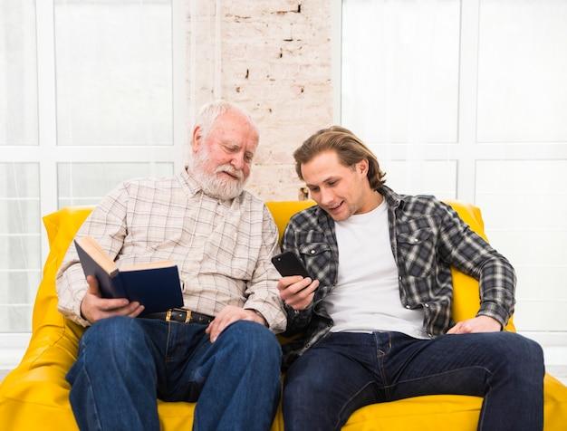Vader en zoon die informatie in celtelefoon doorbladeren
