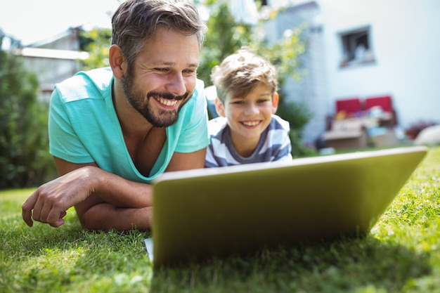Vader en zoon die laptop in tuin met behulp van