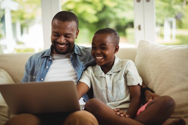 Vader en zoon die laptop in woonkamer met behulp van