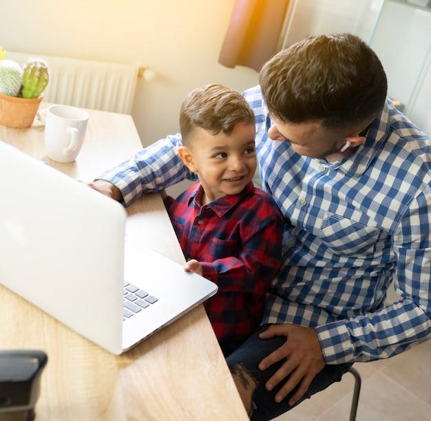 Vader en zoon die laptop thuis met behulp van