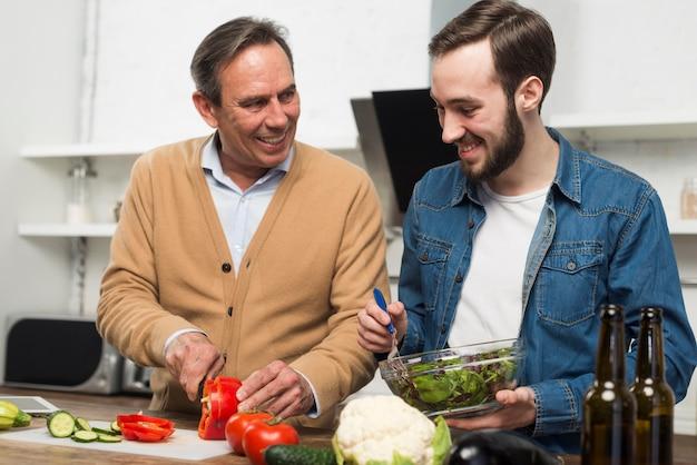 Vader en zoon die maaltijd in keuken voorbereiden