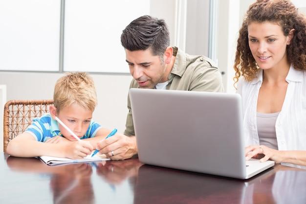 Vader en zoon die met moeder kleuren die laptop met behulp van