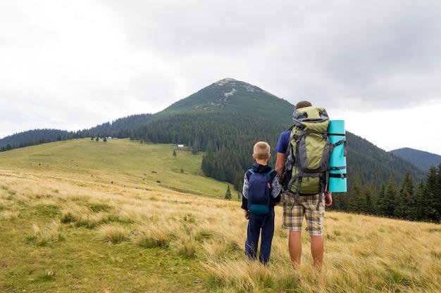 Vader en zoon die met rugzakken samen in de zomerbergen wandelen.