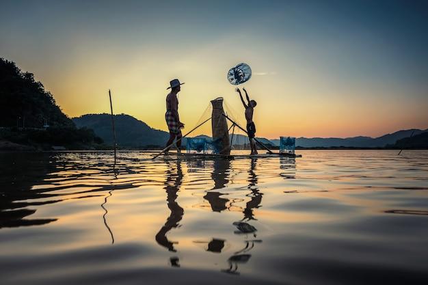 Vader en zoon die op boot bij meer vissen