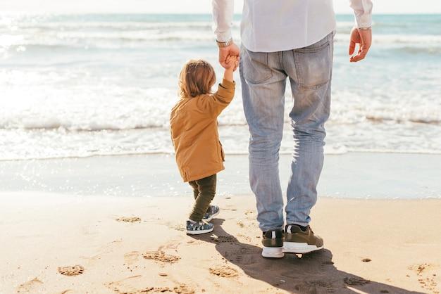 Vader en zoon die op zee kijken
