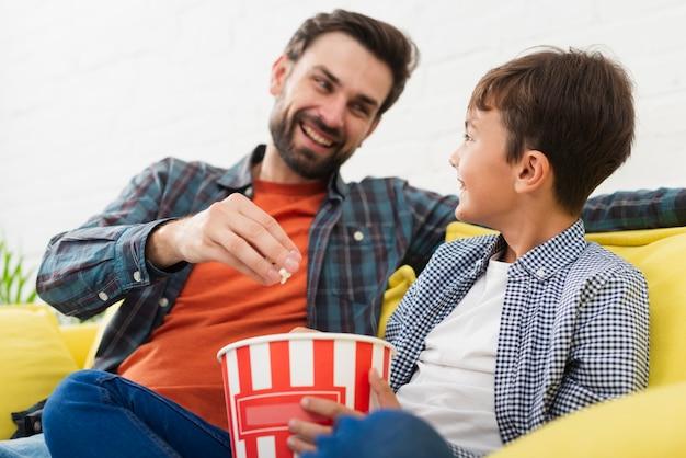 Vader en zoon die popcorn eten en elkaar bekijken