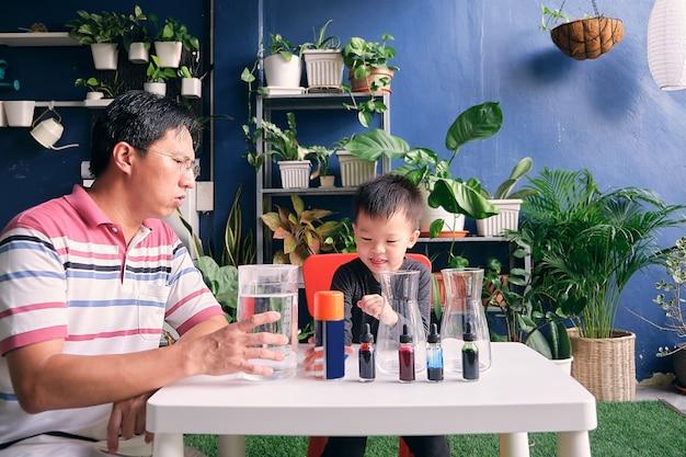Vader en zoon die pret hebben die gemakkelijk wetenschappelijk experiment voorbereiden