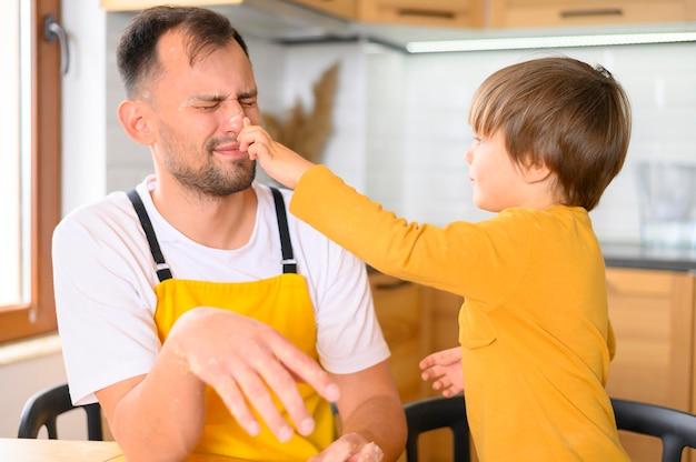 Vader en zoon die rond in de keuken voor de gek houden