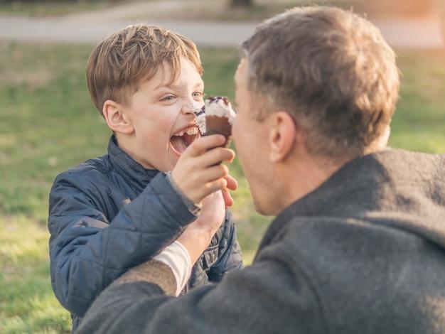 Vader en zoon die roomijs eten en rond voor de gek houden