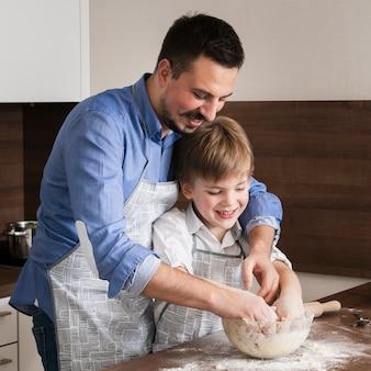 Vader en zoon die samen deeg maken