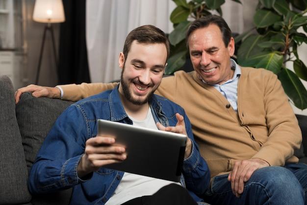 Vader en zoon die tablet in woonkamer bekijken