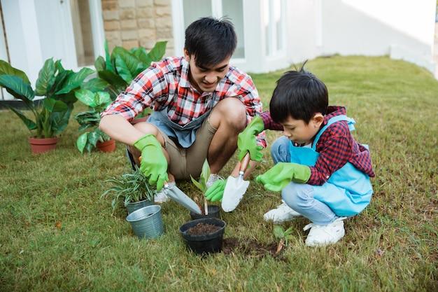 Vader en zoon die thuis in de ochtend tuinieren