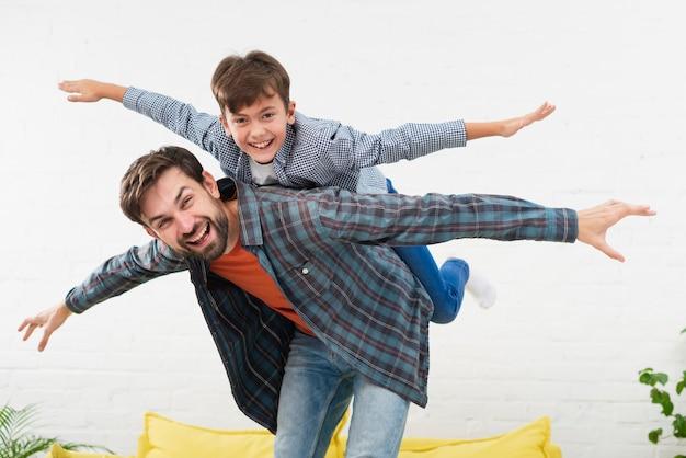 Vader en zoon die vliegtuigen imiteren