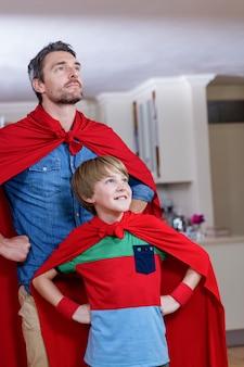 Vader en zoon die zich voordoen als superheld in de woonkamer