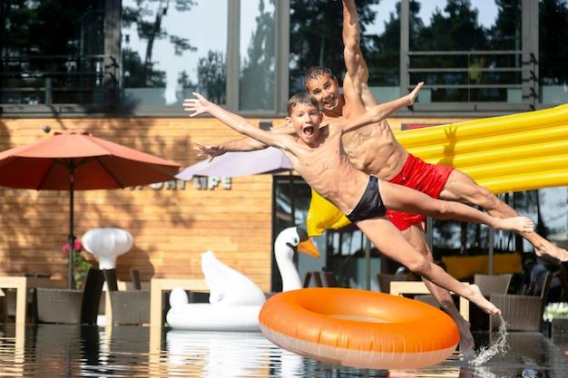 Vader en zoon genieten samen van een dagje aan het zwembad