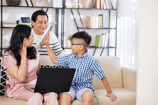 Vader en zoon geven elkaar high five nadat ze moeder hebben overgehaald eten te bestellen of gadgets te kopen