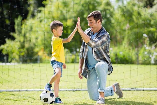 Vader en zoon geven high five in het park