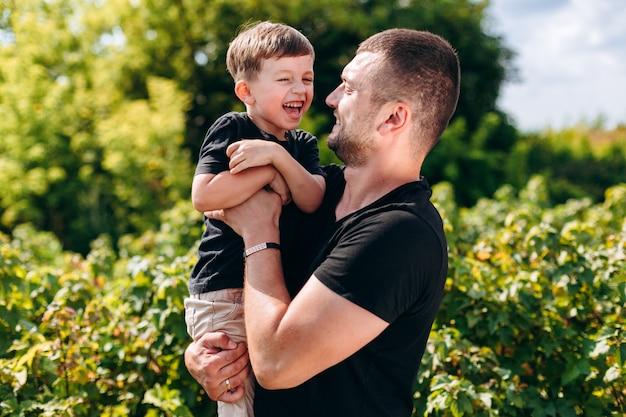 Vader en zoon hebben een grappige tijd buiten, knuffelen en lachen