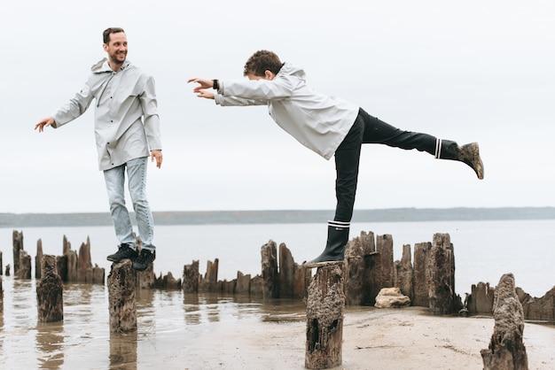 Vader en zoon hebben plezier en doen joga-oefeningen in een regenjas bij de zee
