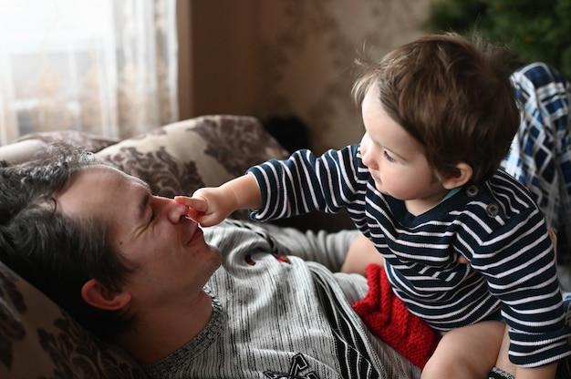 Vader en zoon hebben plezier. vader alleen thuis met een kind samen spelen.