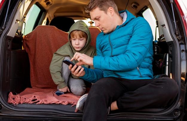 Vader en zoon in de auto met smartphone tijdens een roadtrip