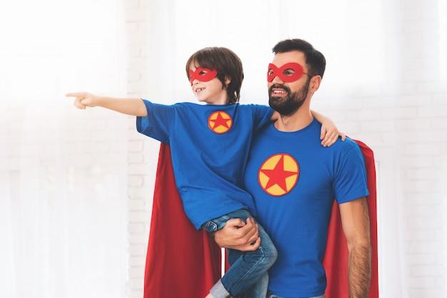 Vader en zoon in de rode en blauwe pakken van superhelden.