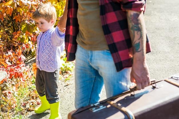 Vader en zoon in het herfstpark spelen een lachend kind en zijn vader is in het herfstpark