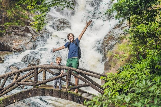 Vader en zoon in het oppervlak van de prachtige trapsgewijze datanla waterval in het bergstadje dalat, vietnam