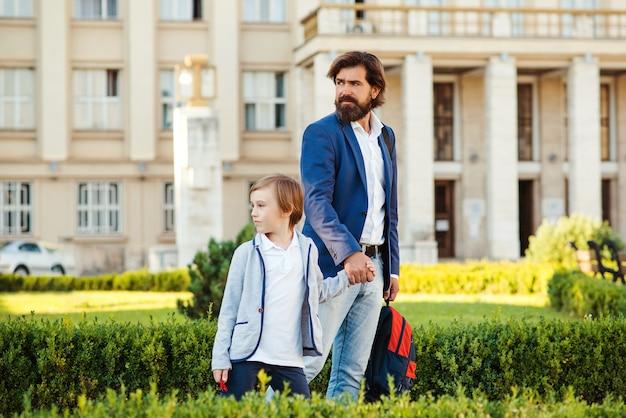 Vader en zoon in pakken die na school lopen. modieuze vader en kind gaan hand in hand. mode, vaderschap en relatie. vader praten met zoon buitenshuis.