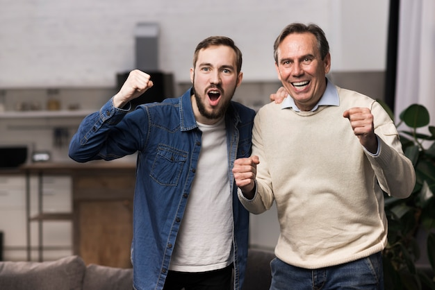 Vader en zoon juichen in woonkamer