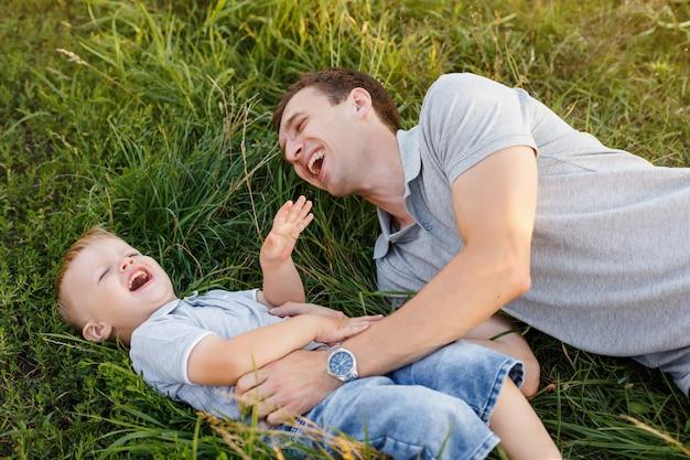 Vader en zoon kietelen elkaar op het gras