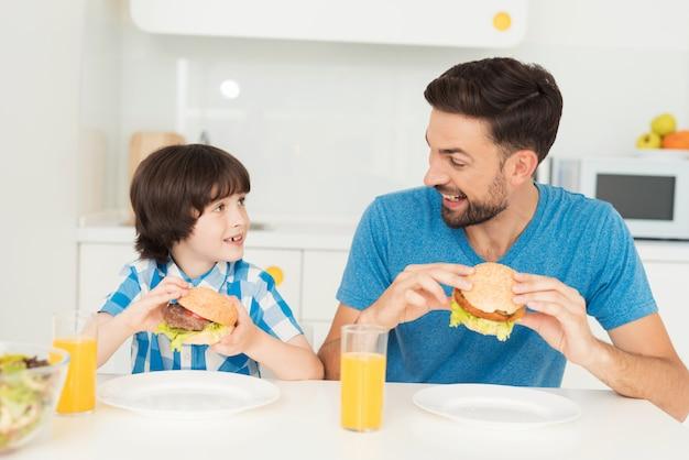 Vader en zoon kijken elkaar aan tijdens het eten.